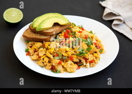 Homemade southwestern egg scramble with toast on a white plate on a black surface, low angle view. Close-up. - Stock Photo