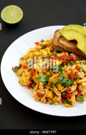 Homemade southwestern egg scramble with toast on a white plate on a black background, side view. Close-up. - Stock Photo