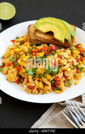 Homemade southwestern egg scramble with toast on a white plate on a black surface, side view. Close-up. - Stock Photo