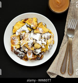 Top view, homemade german Kaiserschmarrn pancake with apple sauce on a black surface. Flat lay, overhead, from above. Close-up. - Stock Photo