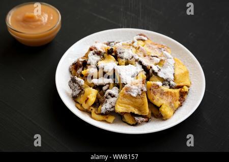 Homemade german Kaiserschmarrn pancake on a black surface, side view. Closeup. - Stock Photo