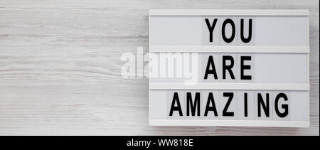 'You are amazing' words on a modern board on a white wooden surface, top view. Overhead, from above. Flat lay. Copy space. - Stock Photo