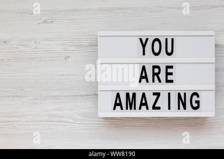 'You are amazing' words on a modern board on a white wooden background, top view. Overhead, from above. Flat lay. Space for text. - Stock Photo