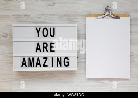 'You are amazing' words on a lightbox, clipboard with blank sheet of paper on a white wooden background, top view. Overhead, from above. Flat lay. Cop - Stock Photo