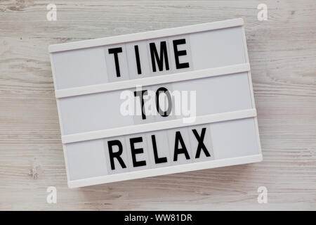 'Time to relax' words on a lightbox over white wooden surface, top view. Overhead, from above. Flat lay. - Stock Photo
