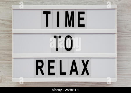'Time to relax' words on a modern board over white wooden background, top view. Overhead, from above. Flat lay. Close-up. - Stock Photo
