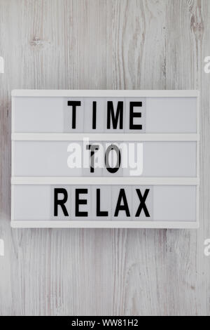 'Time to relax' words on a modern board over white wooden surface, top view. Overhead, from above. Flat lay. Close-up. - Stock Photo