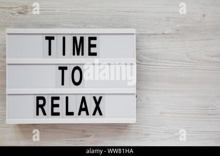 'Time to relax' words on a modern board on a white wooden background, top view. Overhead, from above. Flat lay. Copy space. - Stock Photo