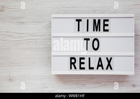 'Time to relax' words on a modern board on a white wooden surface, top view. Overhead, from above. Flat lay. Space for text. - Stock Photo