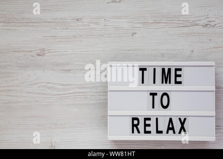'Time to relax' words on a lightbox on a white wooden background, top view. Overhead, from above. Flat lay. Copy space. - Stock Photo