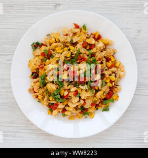 Homemade southwestern egg scramble on a white plate on a white wooden table, top view. Flat lay, overhead, from above. Close-up. - Stock Photo