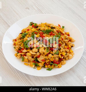 Homemade southwestern egg scramble on a white plate on a white wooden background, side view. Close-up. - Stock Photo