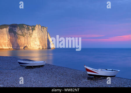 Fishing boats on the beach with view to Falaise d'Aval with Porte d'Aval in the dusk, Etretat, Seine-Maritime, English Channel, Normandy, France - Stock Photo