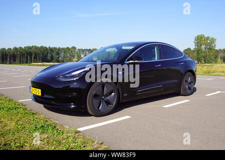 Almere, the Netherlands - August 24, 2019: Black Tesla Model 3 parked on a public parking lot. Nobody in the vehicle. - Stock Photo