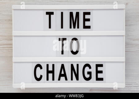 'Time to change' words on a lightbox over white wooden background, top view. Overhead, from above. Flat lay. - Stock Photo