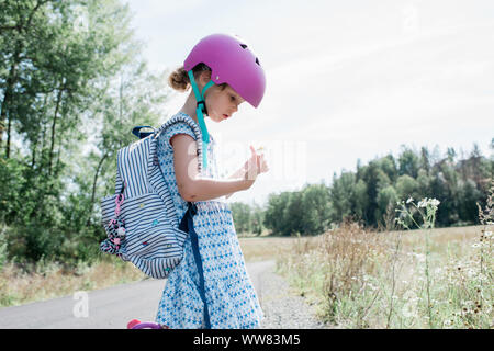young girl with helmet on stopping to look at wild flowers in a meadow