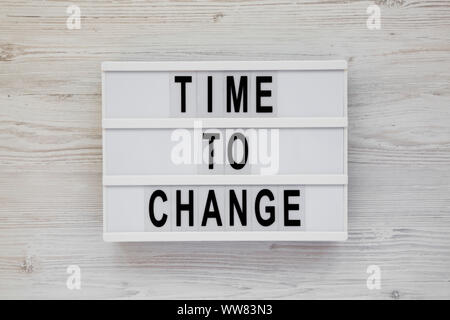'Time to change' words on a modern board over white wooden surface, top view. Overhead, from above. Flat lay. - Stock Photo