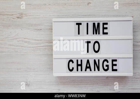'Time to change' words on a modern board over white wooden background, top view. Overhead, from above. Flat lay. Copy space. - Stock Photo