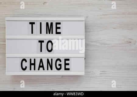 'Time to change' words on a modern board over white wooden surface, top view. Overhead, from above. Flat lay. Space for text. - Stock Photo