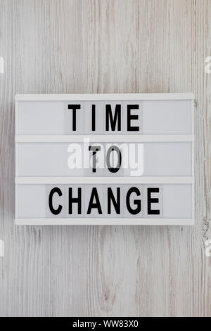'Time to change' words on a lightbox over white wooden background, top view. Overhead, from above. Flat lay. Close-up. - Stock Photo