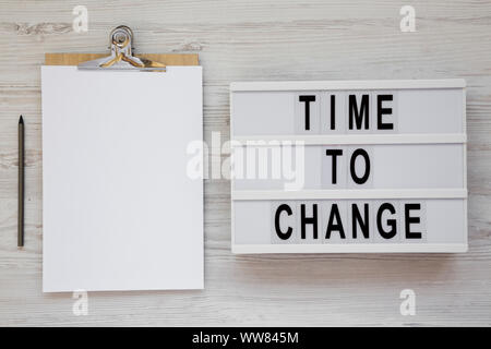 'Time to change' words on a lightbox, clipboard with blank sheet of paper on a white wooden background, top view. Overhead, from above. Flat lay. Copy - Stock Photo