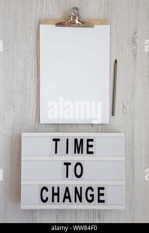 'Time to change' words on a modern board, clipboard with blank sheet of paper on a white wooden background, top view. Overhead, from above. Flat lay. - Stock Photo