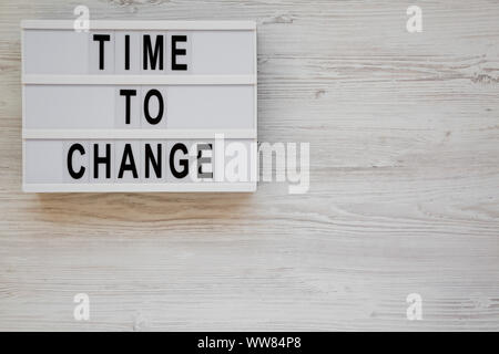 'Time to change' words on a lightbox on a white wooden background, top view. Overhead, from above. Flat lay. Copy space. - Stock Photo
