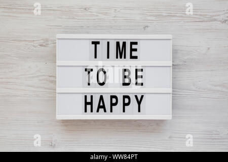 'Time to be happy' words on a modern board on a white wooden background, top view. Overhead, from above. Flat lay. Closeup. - Stock Photo