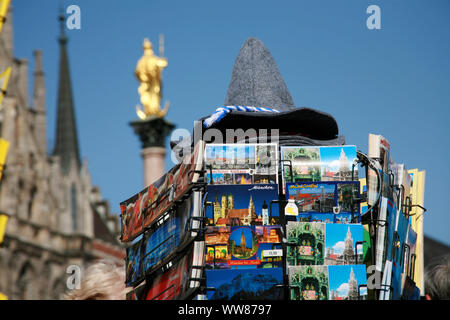 Postcard rack with Bavarian felt hat in front of Munich Marian column - Stock Photo