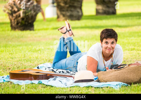 nice beautiful cheerful lady lay down on the grass in relaxing leisure activity outdoor at the park enjoying the day with an acoustic guitar near her young people smile and have fun in spring