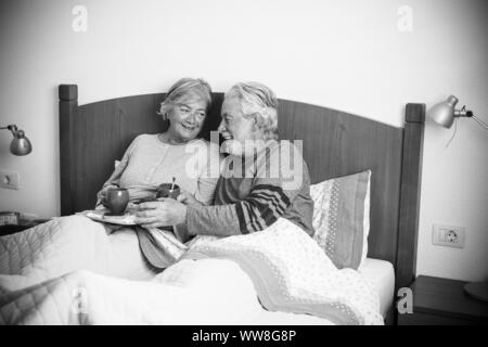 caucasian aged couple doing breakfast at home in the bed, nice natural scene at home for togetherness life concept, love and carefree people married, laughing together starting the day in the morning