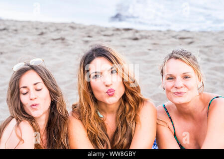 young women in friendship at the beach laying on the sand, sunny day and beautiful girls face expressions staying together enjoying the days of summer - Stock Photo