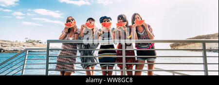 group of happy and cheerful young women girls stand in the summer eating and playing with a red watermelon, ocean in background and vacation holiday concept with friends together - Stock Photo
