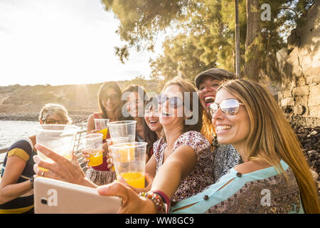 group of young beautiful caucasian woman taking selfie in vacation leisure activity outdoor near the beach and the ocean, sunset time with backlight and lot of smiles and happiness together in friendship forever - Stock Photo