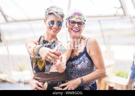 hippy couple of caucasian beautiful females use a smart phone, Different ages nice attractive people stay together in happy leisure activity with friendship, Sharing content on social for cheerful old and young ladies - Stock Photo