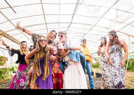 female people dancing together in a festival with traditional colourful dress and hippy clothes, freedom and alternative people enjoying the leisure activity, cheerful women all ages - Stock Photo