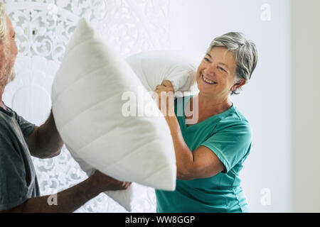 pillows war at home for caucasian couple of playful adult senior man and woman play in the bedroom at the morning, happiness and joy together forever staying young with no age limits, laughing a lot and enjoying the activity at home - Stock Photo