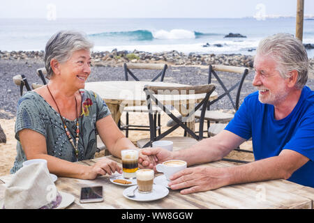Successful retirement recreation, summer vacation concept, Retired mature couple enjoying a beautiful sunny day at the beach, Happy senior woman and man sitting at the bar with wooden tables by the sea, - Stock Photo