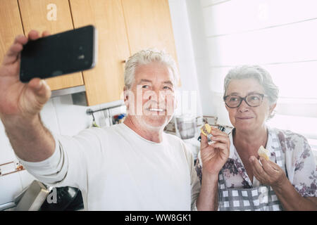 senior adult caucasian happy couple at home in the kitchen cooking and working together with joy and happiness, taking selfie with modern smart phone and eating a piece of cake, love and life forever concept