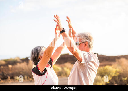 senior mature couple enjoy and win together giving five and hugging under a nice weather day of sun in summer. sport activity and clothes. Active aged people and happiness concept - Stock Photo