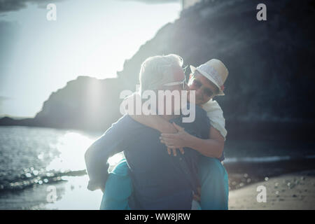 happy senior couple have fun and enjoy outdoor leisure activity at the beach. the man carry the woman on his back to enjoy together a retired lifestyle at the beach - Stock Photo