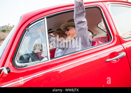 couple od senior traveler enjoyinmg the trip on a old vintage red car. happiness and alternative lifestyle in summer vacation. adult man and woman togetherness driving and having fun - Stock Photo