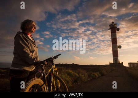 adult senior beautiful caucasian woman biker standing and enjoy the sunset near the coast and the ocean. mountain bikes sport. lighthouse in the backgorund and amazing scenic colored place