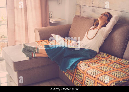 stressed out beautiful middle age woman working at laptop on the sofa at home. internet alternative office for online digital worker. tired looking on the top, wearing funny socks - Stock Photo