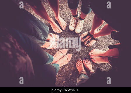 group of woman from high point of view with seven pair of feet with shoes and barefoot without. caucasian ladies in summer time. vintage colors and vignetting and shadow - Stock Photo