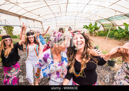 young women and girls in friendship all together celebrating and having fun in a bio natural place. smiles and laughing for group of hippies people alternative concept lifestyle - Stock Photo