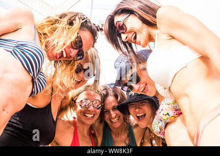nice portrait of seven women females caucasian from the botton point of view in the middle of the group. people happy having fun together in relationship. summer style with swimsuits and nice bodies - Stock Photo