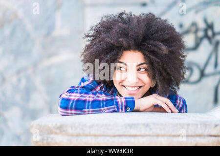portrait of black skin african race of beautiful young girl smiling and looking at her side. enjoying the time and the leisure activity. casual and fashion with afro long hair. beautiful raced model - Stock Photo