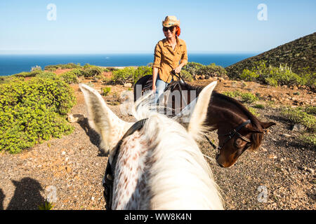 smiling beautiful red hair lady young ride a horse. view from another rider and whit ehorse. leisure activity outdoor with fun in couple. horse therapy discovering great landscape - Stock Photo