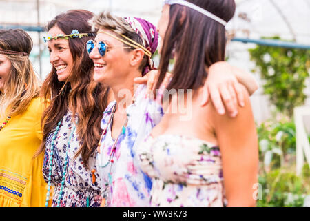 nice group of cacuasian colored clothes young woman stay together in friendship. focus on the brown long hair smiling one. group of happy people in leisure activity outdoor - Stock Photo